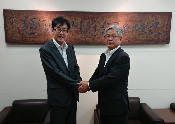 基本合意し握手を交わすオエノンHD西永裕司代表取締役社長と根本市長
